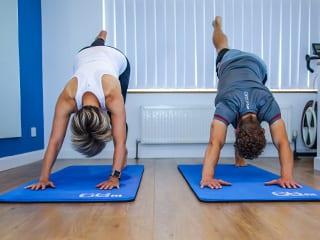 Mike and client doing pilates stretches together