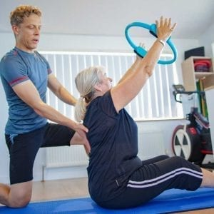 Mike helping a client during a one to one Pilates session