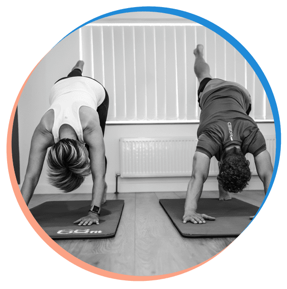 Mike and Becky doing a downward dog during a Pilates studio class